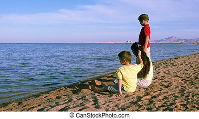 Three kids sitting at the coastline of Red sea in Egypt