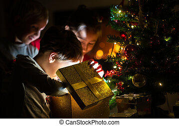 Three kids, two toddler boys and a girl, opening a golden gift box