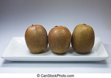 Three Kiwi Above White Dishes