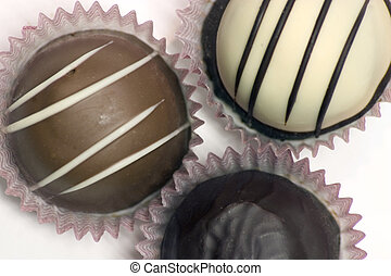 Three different chocolate truffles on a white background.