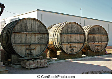 three large wooden barrels for wine stand in the yard