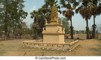 Three-layered Buddhist shrine in an open field - A daylight...
