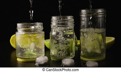 Three lemonade in jars super slow motion