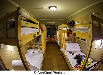 Three-level dormitory beds inside the hostel room for six tourists or students