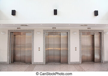 Three lifts with chromeplated doors in an office building hall