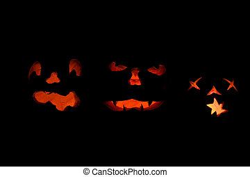 Three lit jack o-lanterns