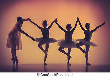 Three little ballerinas dancing with personal ballet teacher...