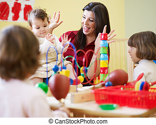 three little girls and female teacher in kindergarten -...