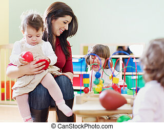 female toddler and 2-3 years girls playing with toys in kindergarten. Horizontal shape, copy space