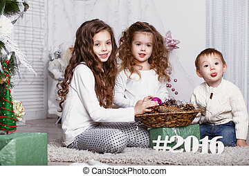three little siblings decorating Christmas tree with fir-cone.