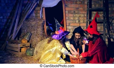Three Little Witches Taking Gifts Out Of Basket At Halloween