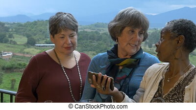 Three lively senior women in 60s on vacation taking selfies...