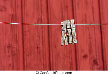 Three lone clothespins on red wall background