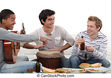 Three male friends playing instruments and eating
