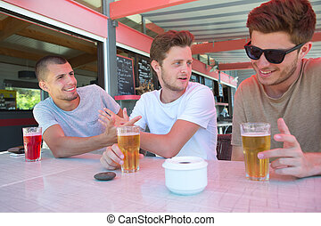 three male friends relax drinking beer at restaurant terrace