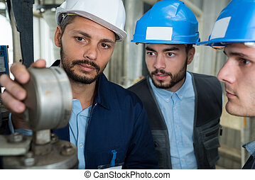 three male workers inspecting gauge on factory machinery