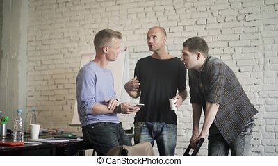 Three males are using app on smartphone and talking to each...