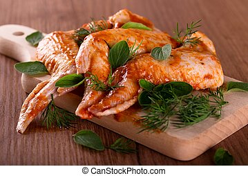 Three marinated chicken wings with herbs