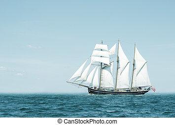 Three mast schooner under sails on the baltic sea. Cross...