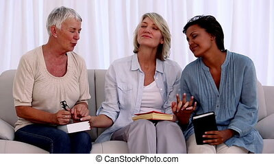 Three mature friends praying together with bibles on the...