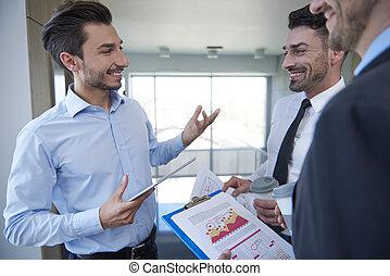 Three men analyzing some data