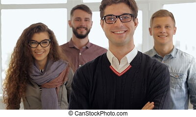 Three men and one woman pose at the office
