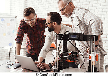 Three men are working on preparing a 3d printer for printing. One of them explains the rest of the subtlety to the print. A young and elderly man is looking at the laptop monitor screen.