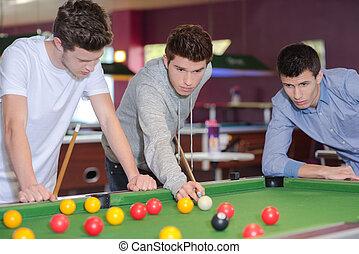 Three men around the pool table