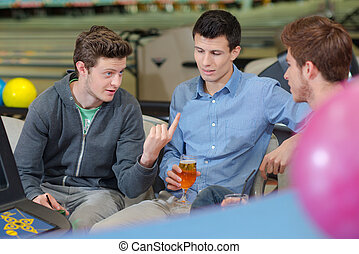 three men having a conversation in the bowling center