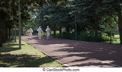 Three men in hazmat suits running on a course way in park