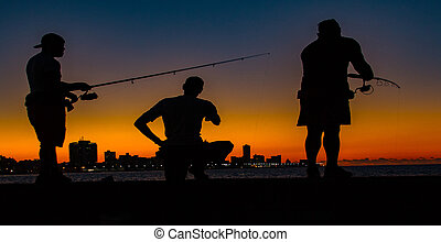 Three men seen in silhouette, fishing from a pier at sundown