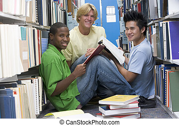 Three men sitting on floor in library with books