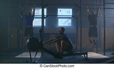 Three men work out together in a fitness room. A man pulls a rowing machine, and two perform pull-UPS on the bar. Cross-training in slow motion.