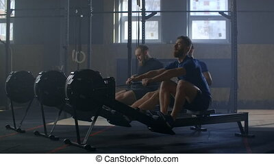 Three men work out together on rowing gym machines slow ...