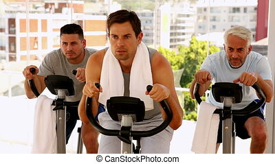 Three men working out on exercise bikes at the gym