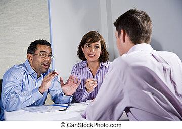 Three mid-adult people sitting at table meeting -...