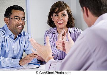 Three mid-adult people sitting at table meeting - ...