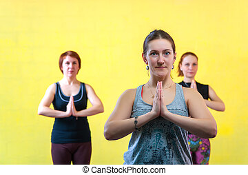 Three middle aged women practicing yoga in class