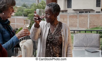 Three mixed racial senior women in 60s celebrating life with...