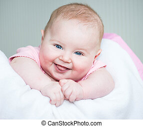 three month old baby - cute smiling baby lye on a bed...