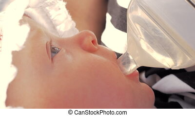 Three months baby drinking water from the bottle outdoor