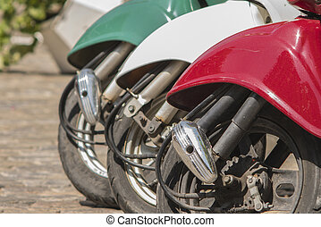 three mopeds painted in colors of the Italian flag