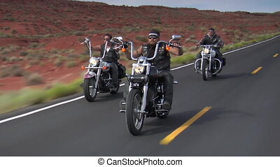 Three motorcyclists ride down desert highway