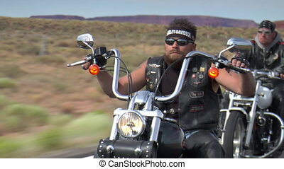 Three motorcyclists ride down desert highway