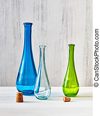 Three multicolored glass bottles with stoppers for saving olive oil on a gray background, a table