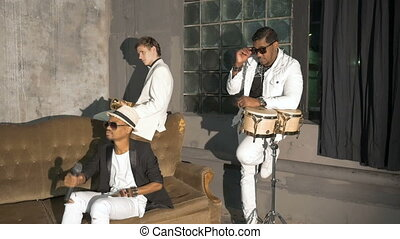 Three musicians participate in the filming of a music video.