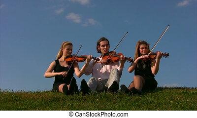three musicians plays violins sits on grass