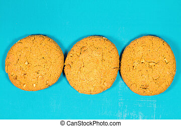Three oatmeal cookies with peanuts on the table