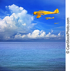 three of yellow plane flying over sea water