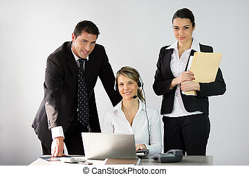 Three office workers around a desk
